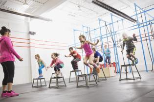 Children doing box jumps at gym