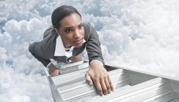 African American businesswoman climbing ladder