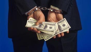 Handcuffed businessman holding cash