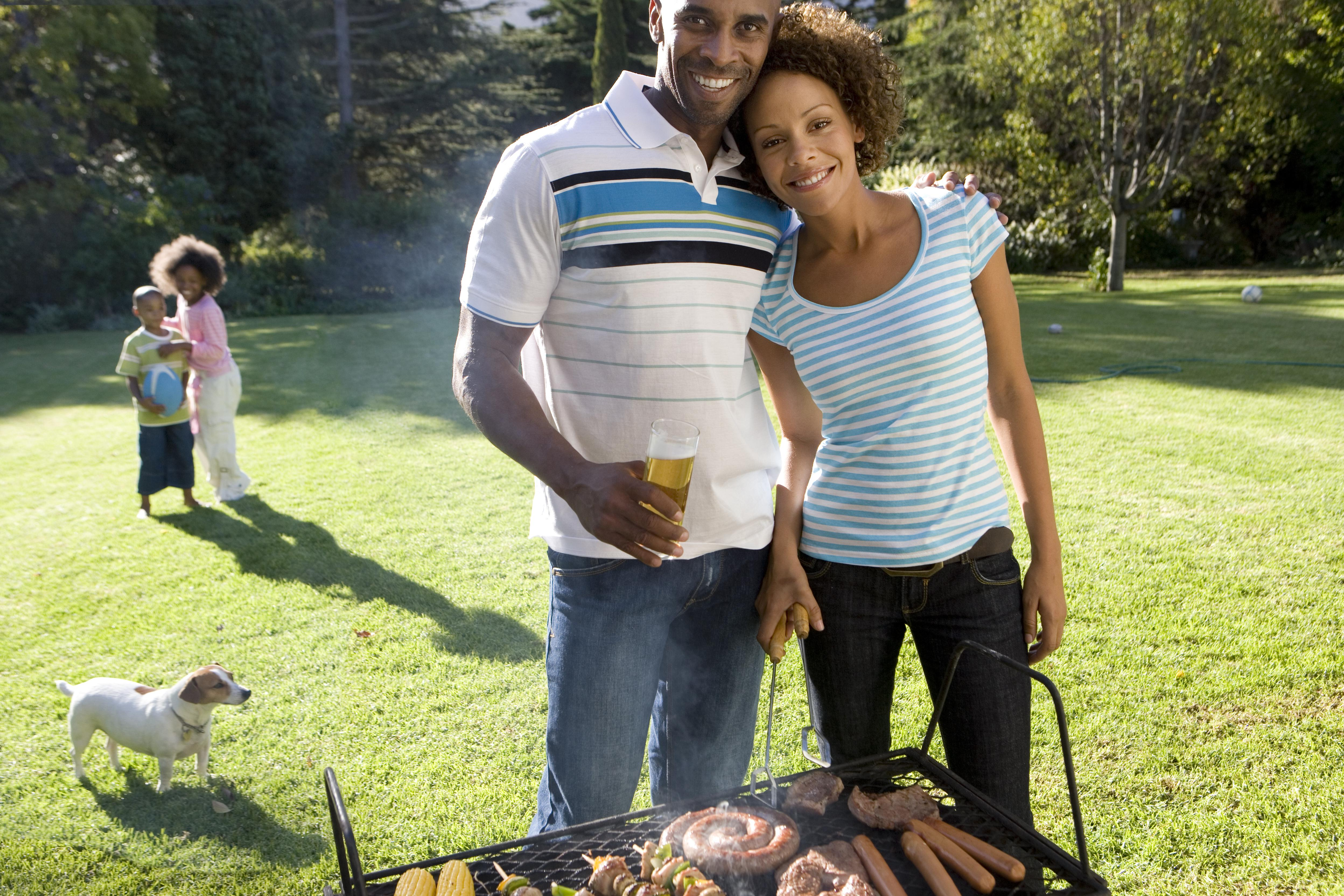 Couple by barbeque, son and daughter (6-10) in background, smiling, portrait