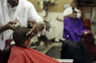 Boy getting hair cut in barber shop