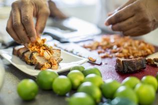 Black chef making pork belly and kimchee in restaurant