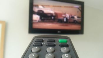 Close-Up Of Remote Control Against Television Set At Home