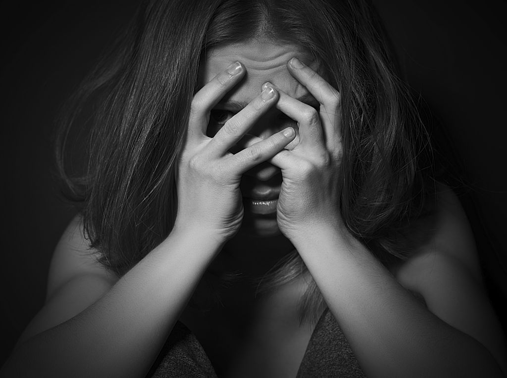 sad woman in depression and despair crying covered her face on black dark background