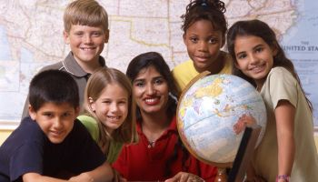 Teacher and students with world globe and laptop