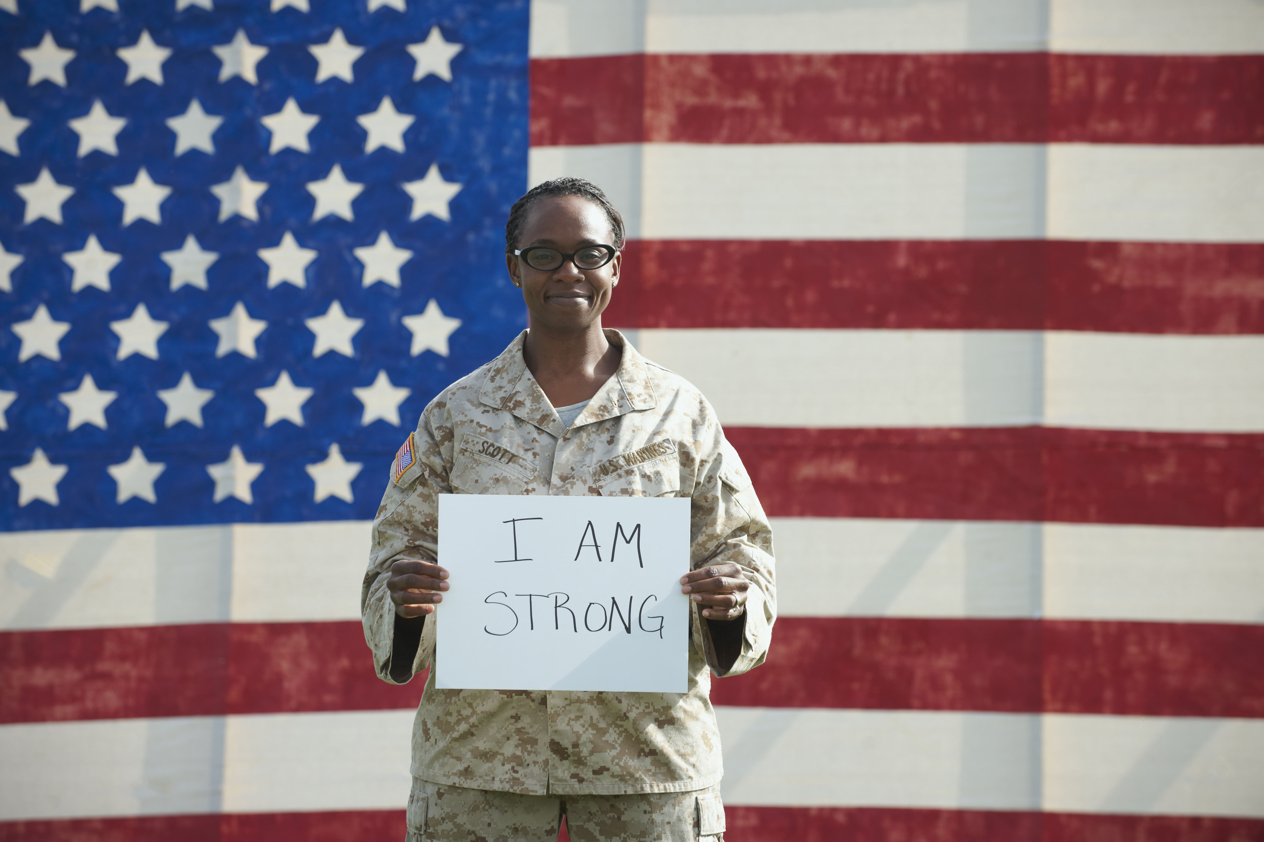 Black soldier holding I am strong sign near American flag