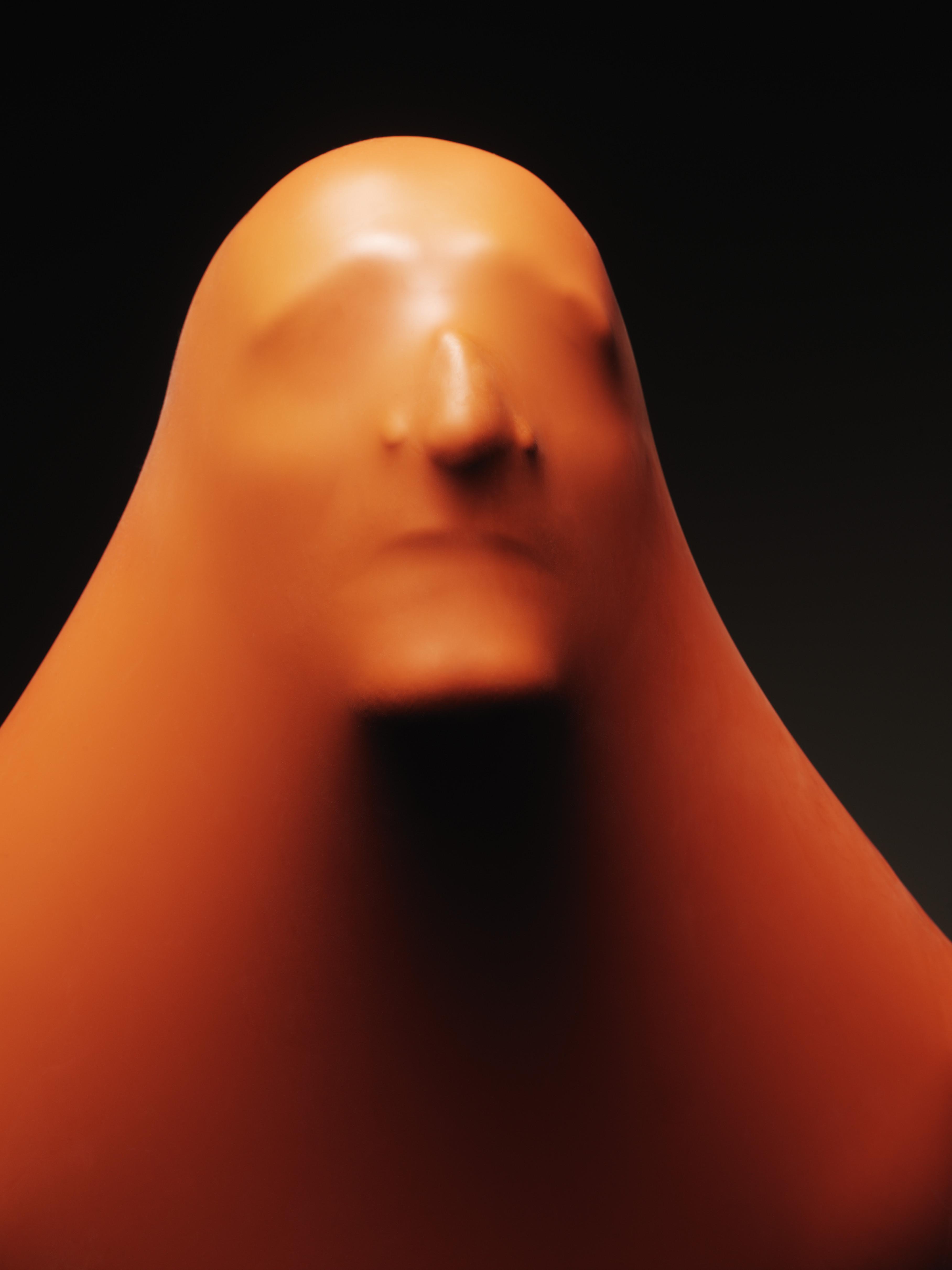 Impression of man's face through orange rubber, close-up