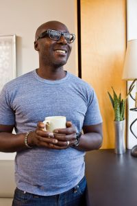 man holding coffee cup looking out window
