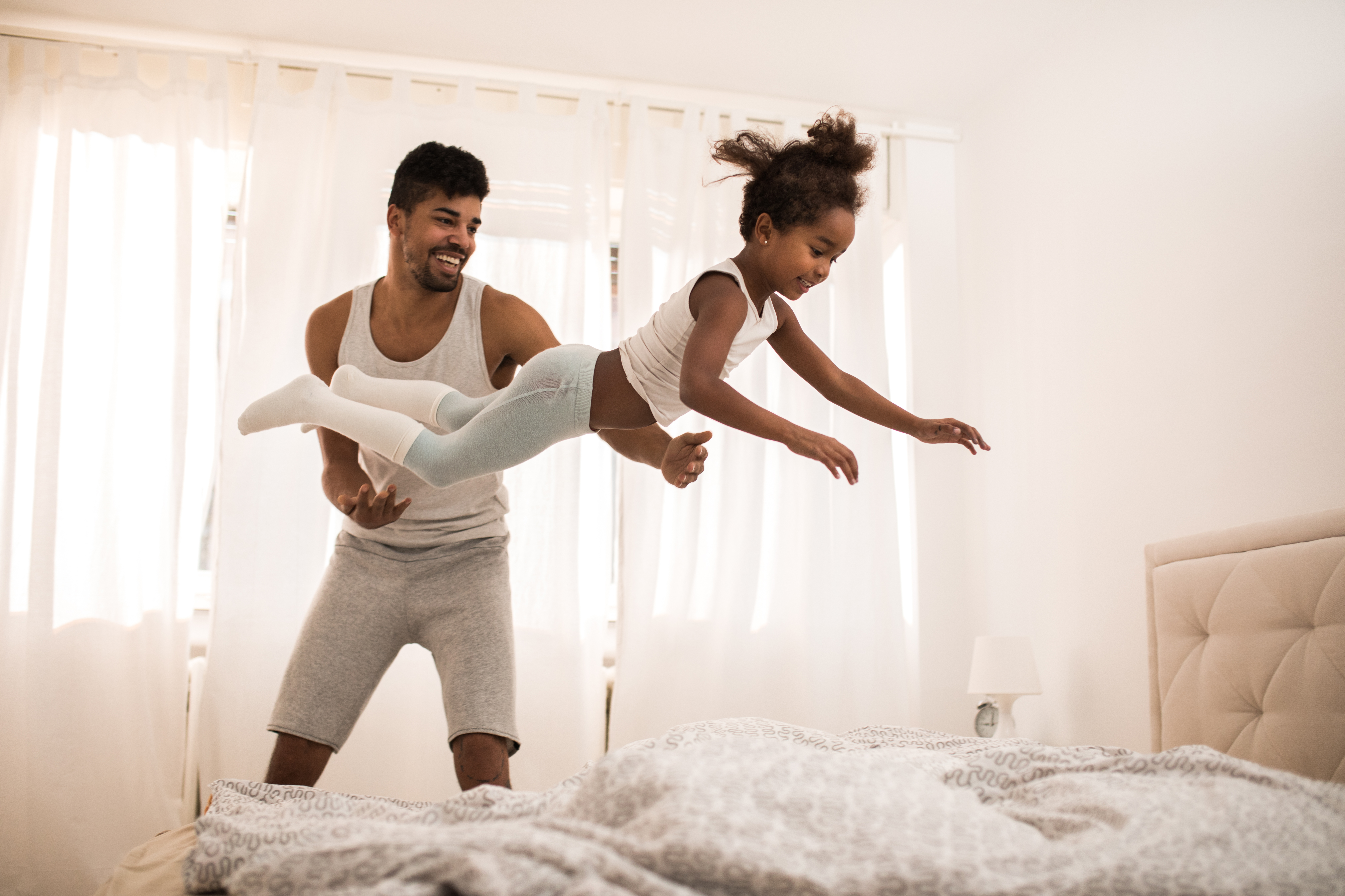Playful black father and daughter having fun in bedroom in the morning.