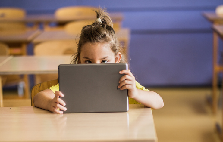 Cute schoolgirl using digital tablet on a class at elementary school.
