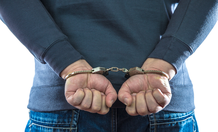 Midsection Of Man Wearing Handcuffs Against White Background