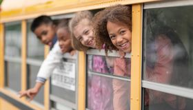 Diverse group of students look out school bus windows