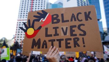 "Protesters display a huge placard reading ""Black Lives..."