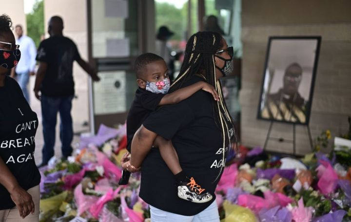 Woman & Daughter Wait To VIew Casket
