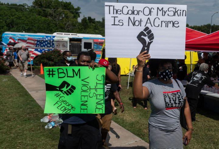 People Holding Black Lives Matter Signs
